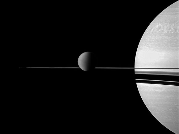 The Cassini spacecraft views Saturn with a selection of its moons in varying sizes. Titan is in the center of the image, while smaller moon Enceladus is on the far right.