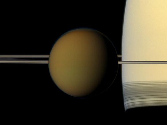 The colorful globe of Saturn's largest moon, Titan, passes in front of the planet and its rings in this true color snapshot from NASA's Cassini spacecraft.