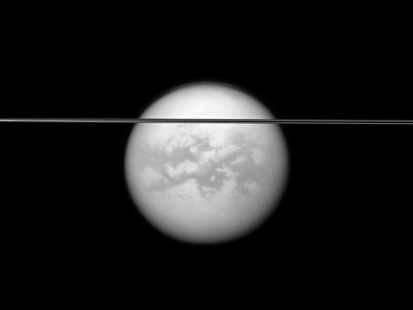 Saturn's rings cut across this view of the planet's largest moon, Titan.