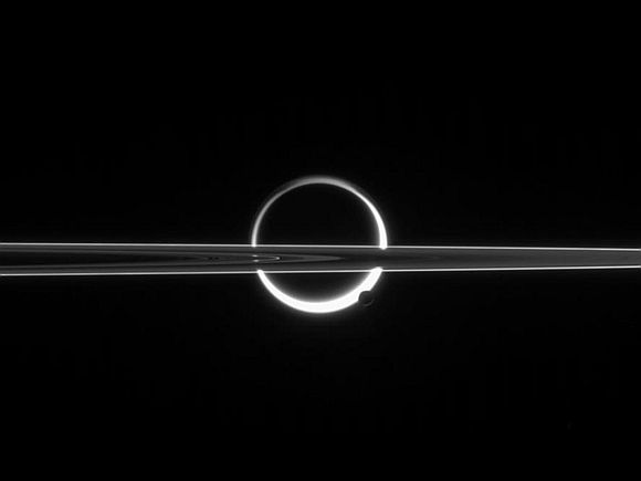 Saturn's rings cut across an eerie scene that is ruled by Titan's luminous crescent and globe-encircling haze, broken by the small moon Enceladus, whose icy jets are dimly visible at its south pole.