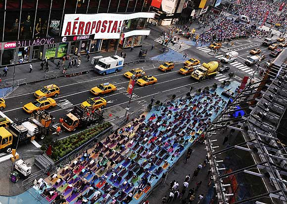 People practice yoga on the morning of the summer solstice in New York's Times Square