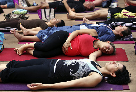 A pregnant woman touches her stomach as people practice yoga on the morning of the summer solstice in New York's Times Square