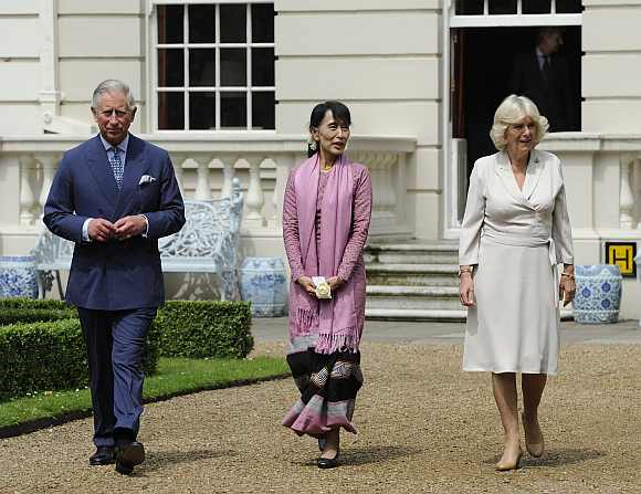 Suu Kyi walks with Britain's Prince Charles and Camilla, Duchess of Cornwall in the gardens of Clarence House in central London