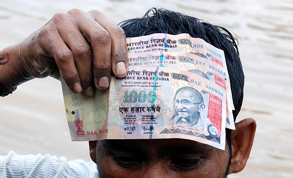A man holds up the Rs 1,000  notes he found in the water body