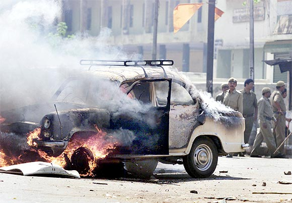 Policemen watch a car set ablaze by rioters in the street in Ahmedabad, during the 2002 riots