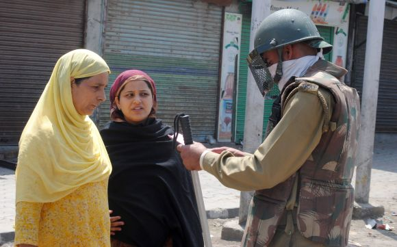A security personnel checks the identification papers of locals as strict shutdown was observed for the second day in Srinagar