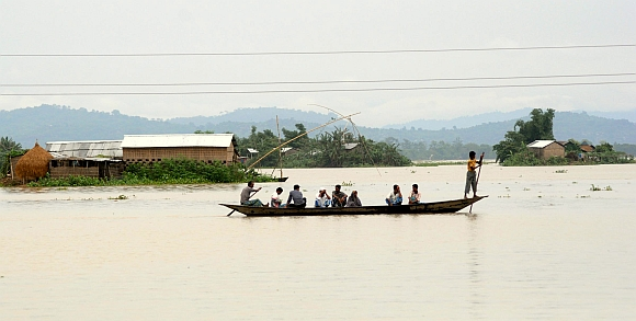 Flood victims travel through affected areas of Ashigarh village in Morigoan district