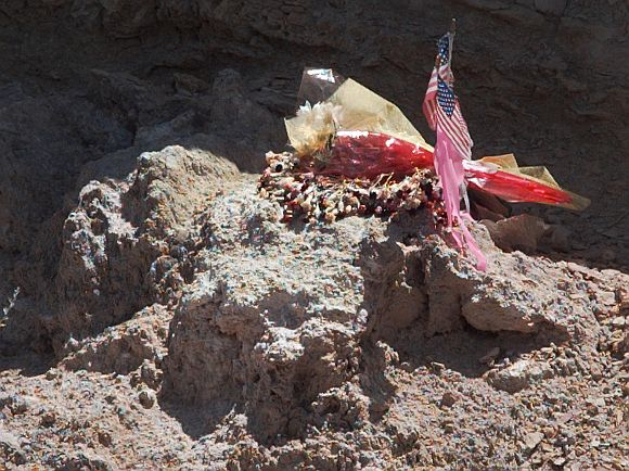 A portion of the site where a UFO allegedly crashed near Roswell in 1947 is marked with flowers and two small US flags.