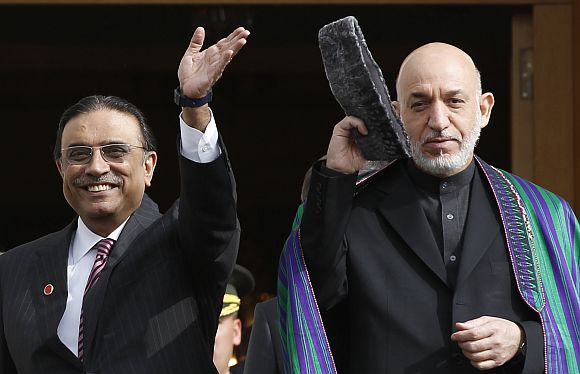 Pakistan President Zardari poses for a photograph with his Afghan counterpart Karzai, in Istanbul