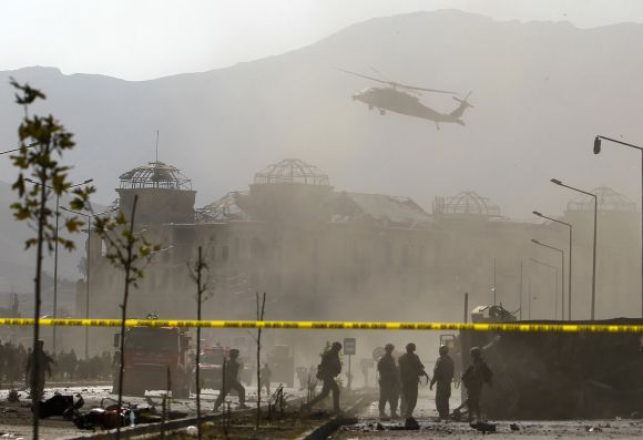 A NATO helicopter flies over the site of a bomb blast in Kabul
