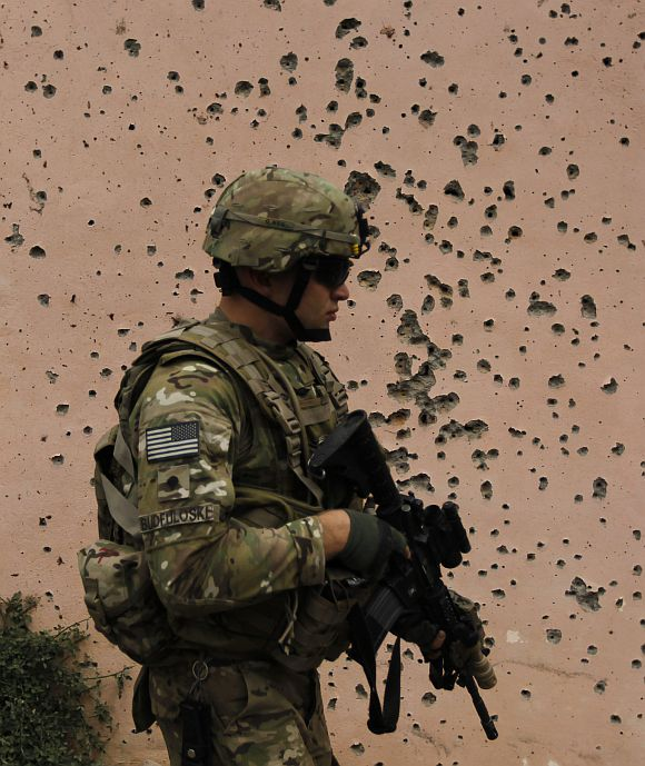 A US soldier walks past a bullet-riddled wall after an attack at the compound of the governor of Parwan province in Afghanistan