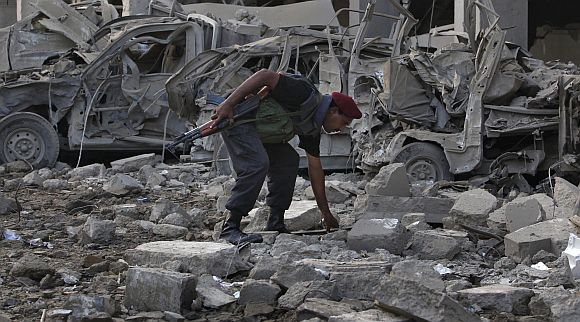 A paramilitary soldier goes through the rubbles of a building after it was destroyed in a suicide bomb attack in Karachi