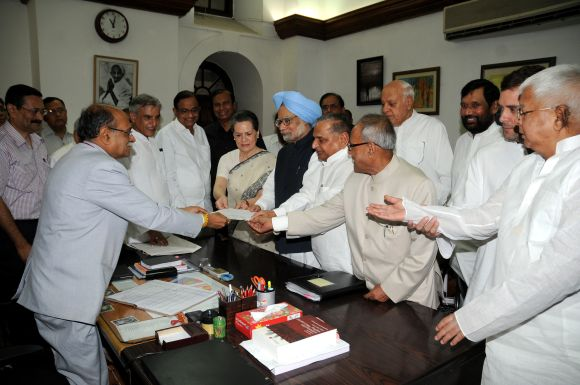 Pranab Mukherjee, flanked by UPA leaders and the PM, files his nomination for the President's post