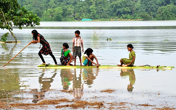 Flood affected children are seen using a boat made out of banana leaves in Morigoan district, about 80 Km from Guwahati