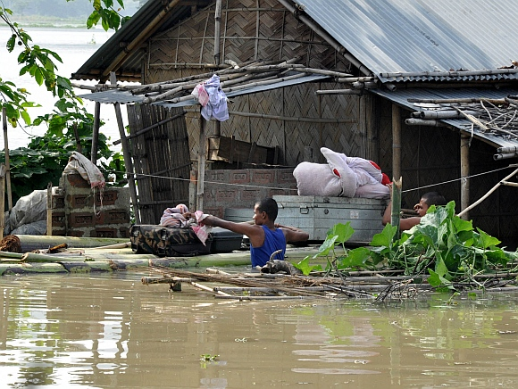 A man tries to salvage his belongings from his flood ravaged home