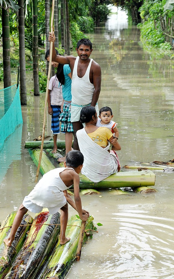 A family wades through flood waters on a boat made out of a banana tree