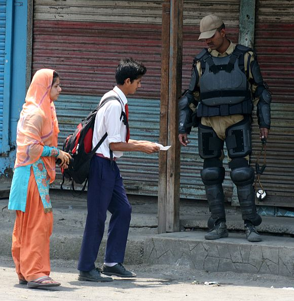 A school child shows identification papers to a security personnel as shutdown crippled life in Srinagar on Friday