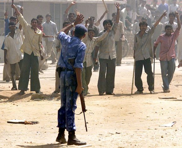 Armed mobs confront a policemen during the horrific Gujarat riots of 2002