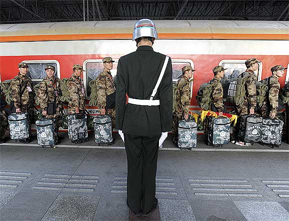 A soldier stands guard as recruits walk in a line before boarding a train at the railway station in Nanjing, Jiangsu province, China