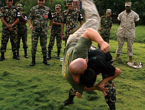 A Nepal army soldier executes a shoulder throw on US Marine, during a martial arts demonstration in Kathmandu, Nepal