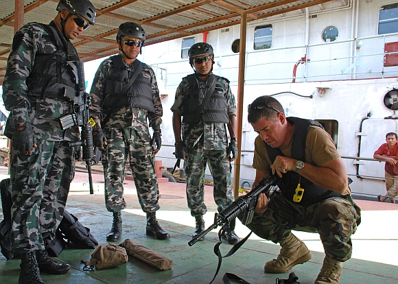 A US soldier does follow-up clearance checks on Bangladesh Navy sailors' weapons