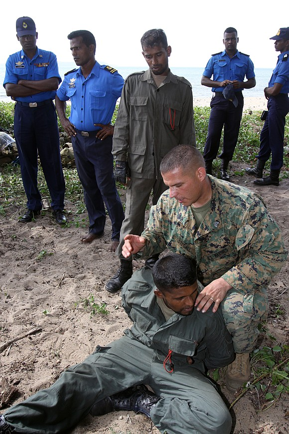 A US Marine demonstrates search techniques to sailors of the Sri Lankan Navy's Special Boat Squadron