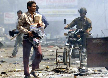 A man carries goods looted from a shop in riot-torn Ahmedabad while a policeman looks on.