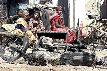 A riot-hit family from Ahmedabad outside their damaged house