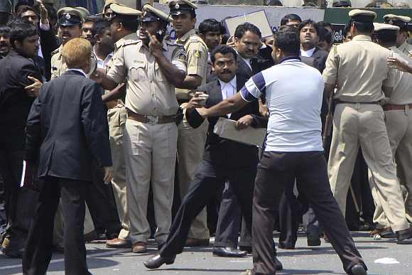 Police try to control a violent lawyer outside the court premises in Bengaluru