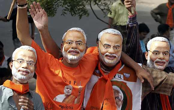 Supporters of the BJP wear masks of Modi in Ahmedabad