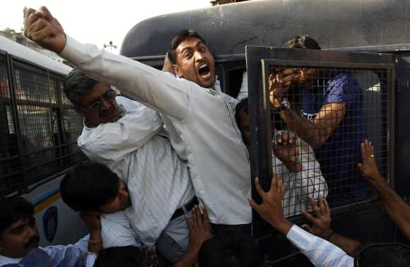 A survivor of the Godhra riot shouts anti-government slogans as he is detained by police during a protest to commemorate its 10th anniversary in Ahmedabad