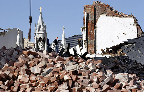 A man takes part in the clean up of St. Joseph's Catholic Church which was destroyed by a tornado in Ridgway, Illinois