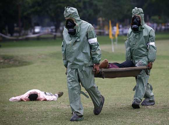 Soldiers carry a man acting as an injury victim on a stretcher during an exercise to prepare for chemical and biological terror attacks