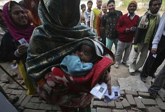 A woman holds her baby and her voter identity card as she waits for her turn to cast her ballot at a polling station