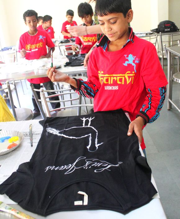 Underprivileged children from Mumbai paint a T-shirt as part of the 1000 Crane Project