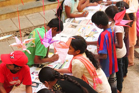 Underprivileged children busy making origami cranes during the 1000 Crane Project in Mumbai