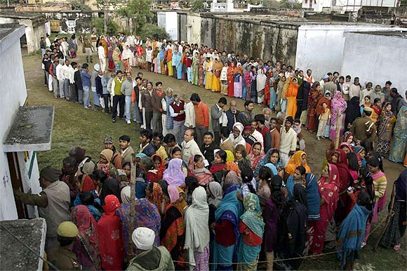 Voters queue up outside a polling centre to cast their vote in Haraiya, Uttar Pradesh
