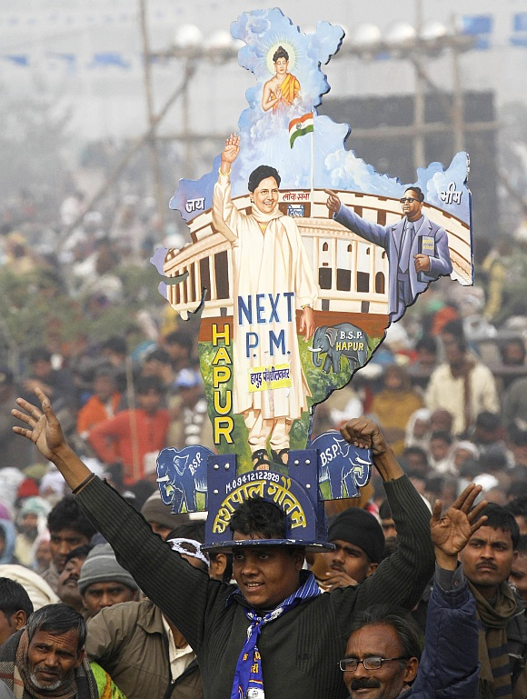 A BSP supporter with a cutout of a map of India with images of Mayawati and B R Ambedkar during an election rally