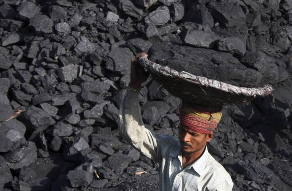 A labourer carries coal in a basket to load it in a truck at a coal store in Chandigarh