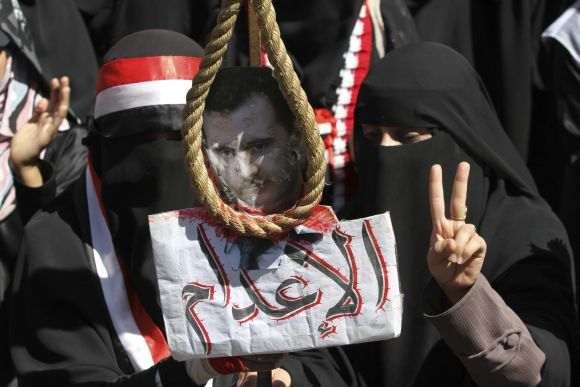 Anti-government protestors hold a picture of Syrian President Assad with a noose