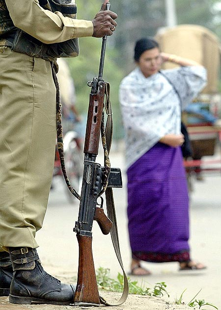 A paramilitary soldier stands guard beside a busy street in Manipur