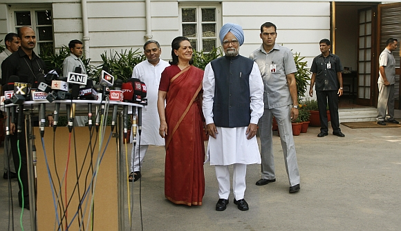 Congress Party chief Sonia Gandhi and Prime Minister Manmohan Singh pose for photographers at 10, Janpath in New Delhi
