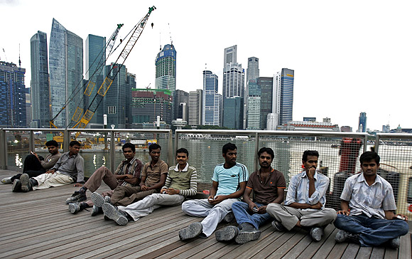 Migrant workers from the Indian sub-continent on their day off sit on an outdoor viewing platform at the recently opened Marina Bay Sands integrated resorts in Singapore
