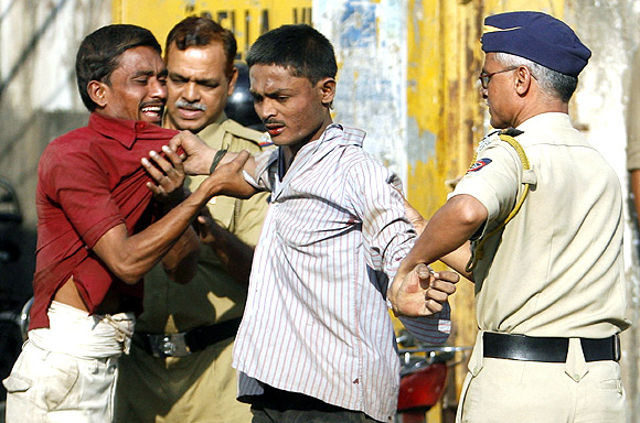Policemen break up a quarrel between migrant workers at a street corner in Mumbai
