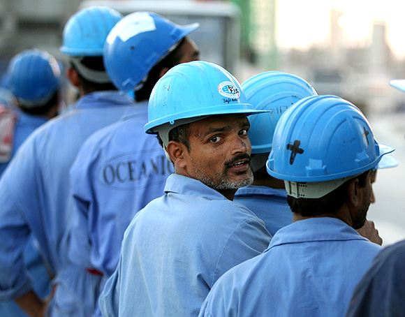 Indian workers line up to board a bus after a day's work in Dubai