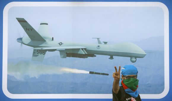 A supporter of Jamaat-e-Islami flashes victory sign in front of a poster of US drone to protest against the alleged killing of Ilyas Kashmiri