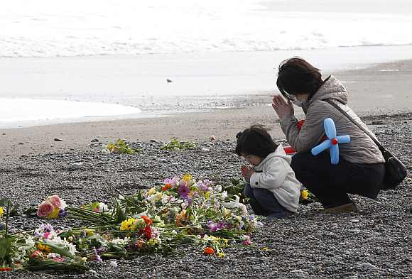A mother and her daughter offer prayers for victims of the March 11, 2011 earthquake and tsunami disaster at a seaside which was damaged by the disaster in Iwaki, Fukushima prefecture to mark the first anniversary of the earthquake and tsunami that killed