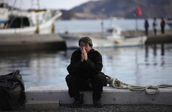 A man takes part in a moment of silence during a ceremony at an area damaged by March 11, 2011 earthquake and tsunami in Ofunato, Iwate Prefecture