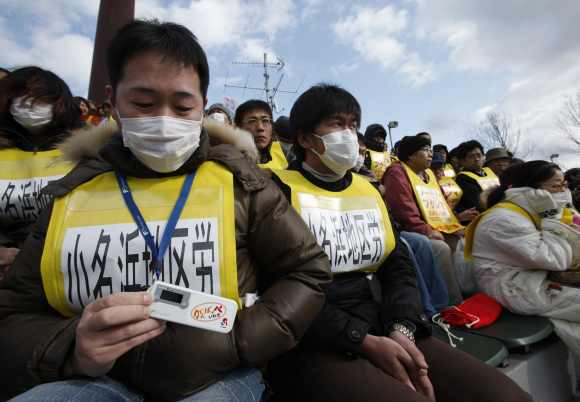 A protester shows his radiation dosimeter as he attends an anti-nuclear rally in Koriyama, Fukushima prefecture