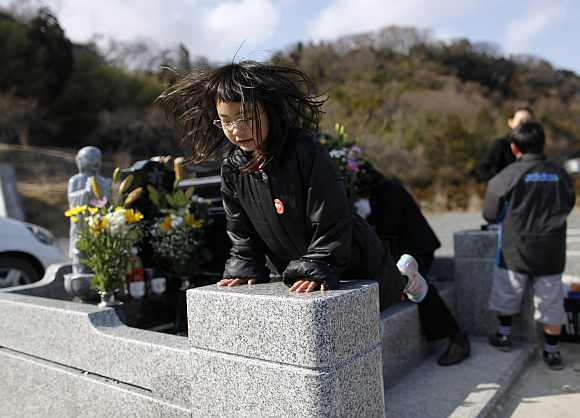 Wakana Kumagai, 7, jumps on the grave of her father, who was killed by the tsunami, in Higashimatsushima, Miyagi prefecture